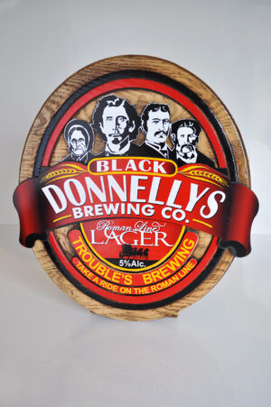 A Black Donnellys Brewing Company Wooden Logo Sign In Black, White, Red, And Yellow.