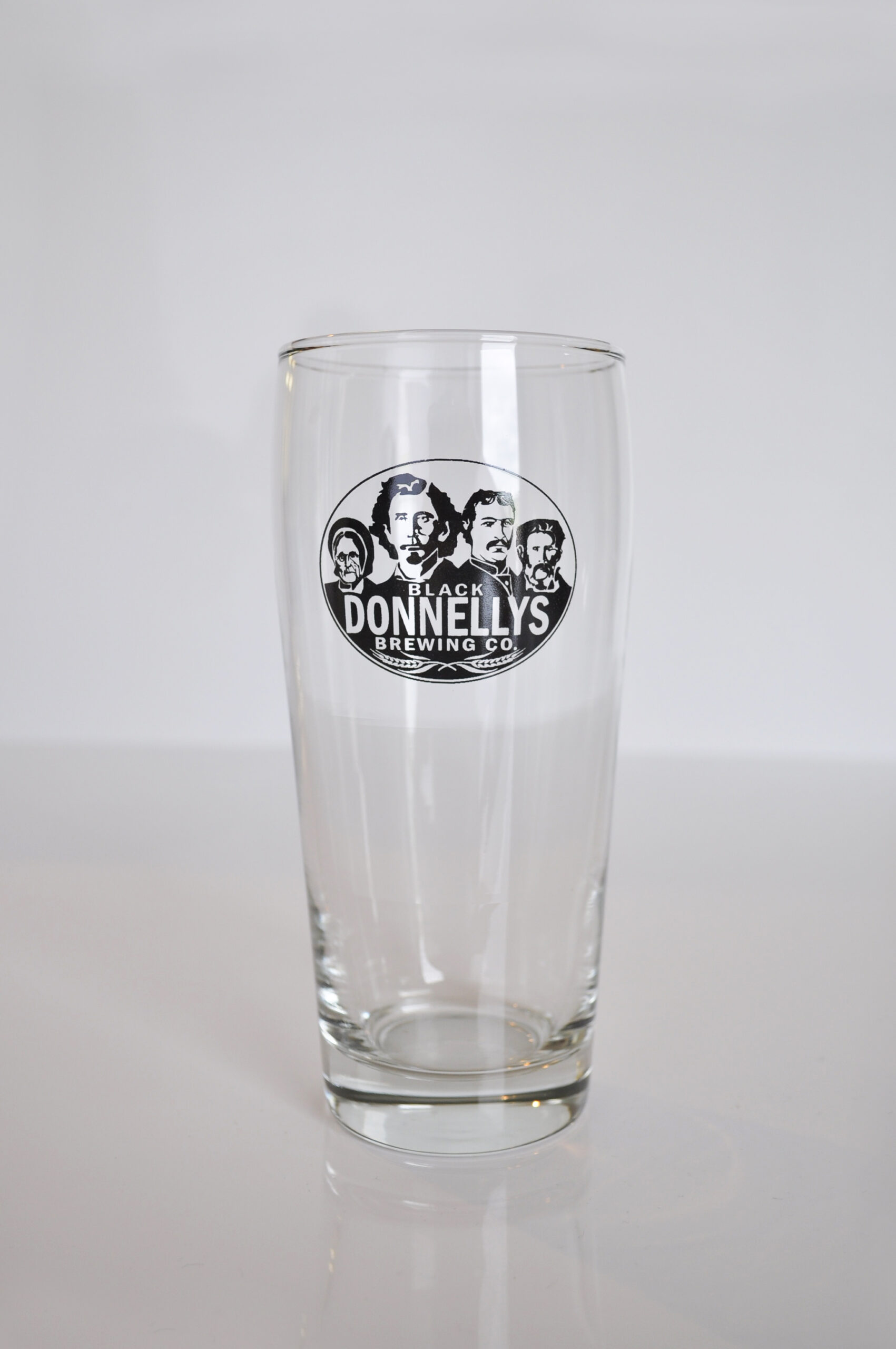 A tall Black Donnellys Brewing Company beer glass decorated with the company logo.