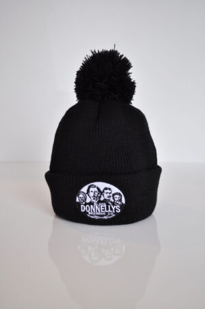 A Black Donnellys Brewing Company Toque Style Winter Hat Topped With Pom-pom And Black And White Company Logo On The Folded Brim.